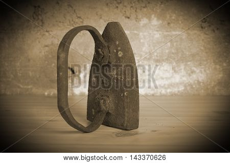An old vintage rusty iron on a wooden board sepia tone