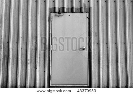 iron door on corrugated metal sheet black and white photo