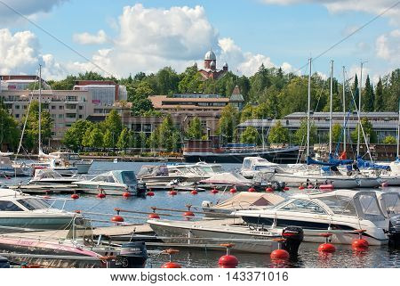 LAPPEENRANTA, FINLAND - AUGUST 8, 2016: Boats and yachts in a harbor of Saimee Lake. On the background is City Lutheran Church.