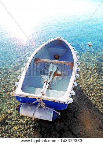 Little anchored raw boat and turquoise sea.