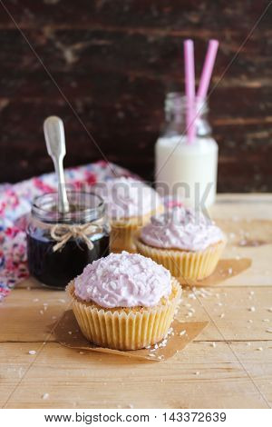 Homemade cupcakes with berry jam and cream cheese with a jar of jam and a bottle of milk on a wooden table, selective focus