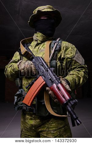 Portrait of soldier in black mask with a gun on dark background