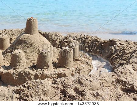 Sand castle on the beach with turquoise sea.