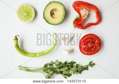 guacamole ingredients on white background: avocado, paprika, tomato, onion