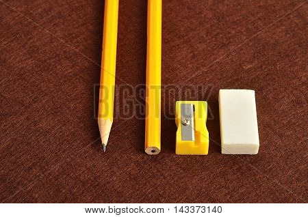 A sharpener eraser and two yellow pencil isolated on a brown background