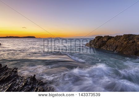 Sunset at Currumbin Rock Gold Coast with ocean current sweeping across the rocks.