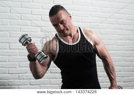 Young Man Exercise Biceps With Dumbbells