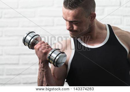 Man Exercising Biceps On White Bricks Background