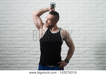 Triceps Exercise With Dumbbells On White Bricks Background