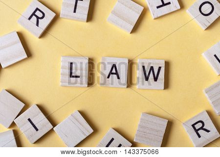 Law word written on wood block. Woodwn abc.