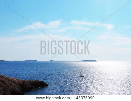 Sparkling sea scene with islands and sailing ship.