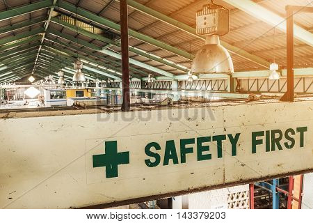 Safety first label with a background in industrial production linesFocus on label