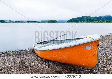 Small orange row boat parks at shore at lake Kawaguchiko Japan on a cold and cloudy sky evening