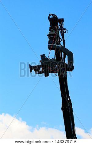 Professional TV camera on a crane against sky.