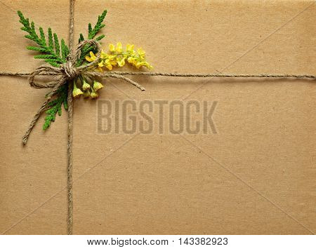 Brown cardboard tied with small wild flowers bouquet and rope. Summer present.