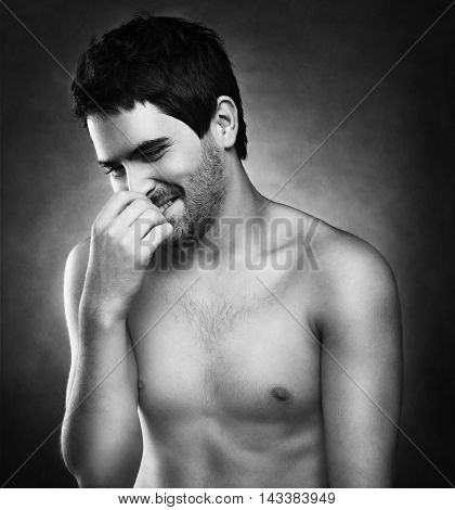 Handsome Man Laughing While Covering His Mouth With On A Dark Background