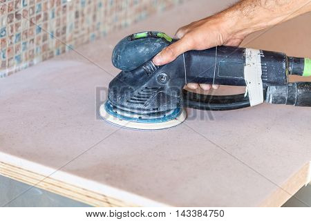 Worker Sanding Countertop From Artificial Stone