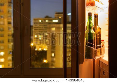 Open Refrigerator With Wine Bottles In Night