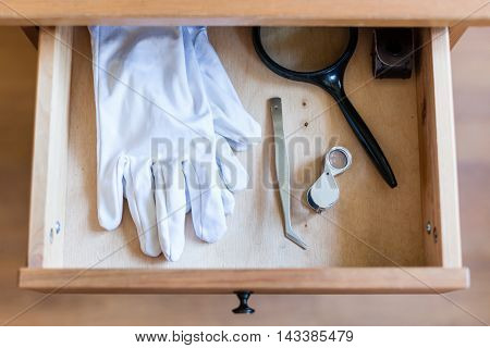 Magnifier, Forceps And White Gloves In Open Drawer