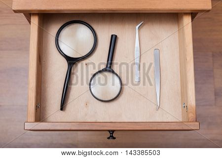 Magnifying Glasses And Tweezers In Open Drawer