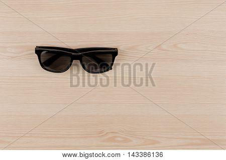 Black vintage sun glasses on wood top view