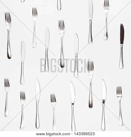 Table Knives And Forks Arranged On White