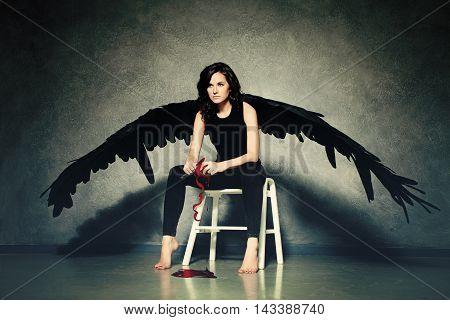 Cruel Love. Woman Black Angel Peeling a Red Heart
