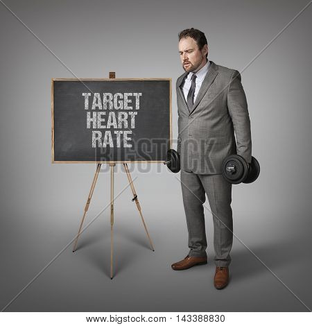 Target heart rate text on blackboard with businesssman holding weights
