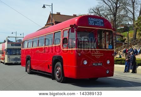 FELIXSTOWE, SUFFOLK, ENGLAND - MAY 01, 2016: Classic Red London Transport Bus being driven on the road.