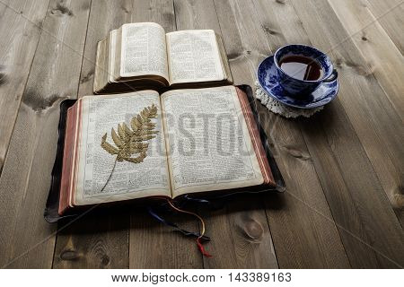 Christian Bible study scene of two open Bibles showing old and new testaments with cup of tea on wooden table background. Bibles are non trademark version.