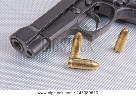 Gold bullets and gun on aluminium background