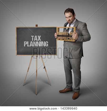 Tax planning text on blackboard with businessman and abacus