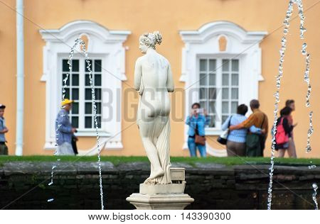 PETERHOF, SAINT - PETERSBURG, RUSSIA - AUGUST 19, 2016: The Upper Garden. People take pictures near Western Square Pond Fountain and Venus Italica Sculpture