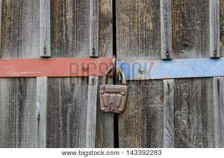 Wooden texture old deadbolt colored lining and a padlock