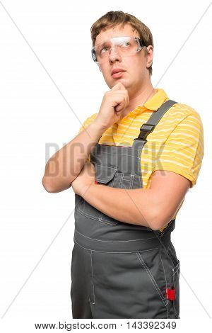 Vertical portrait of a pensive mechanic in overalls on a white background
