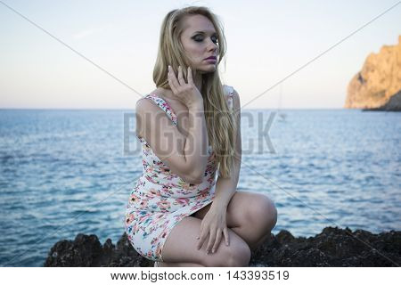 Travel, blonde dressed in floral dress in a cove on the island of Mallorca next to the Mediterranean Sea