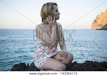 happy blonde dressed in floral dress in a cove on the island of Mallorca next to the Mediterranean Sea