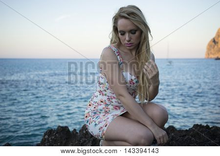 romantic blonde dressed in floral dress in a cove on the island of Mallorca next to the Mediterranean Sea