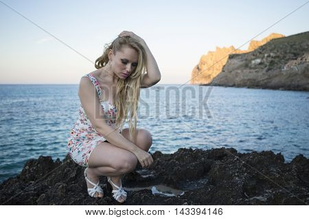sexy blonde dressed in floral dress in a cove on the island of Mallorca next to the Mediterranean Sea
