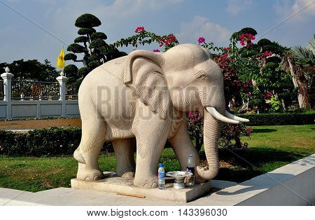 Samut Prakan Thailand - January 15 2013: Statue of a revered Thai elephant complete with two plastic bottles of water left as offerings at Wat Asoke