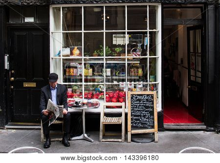 KING'S CROSS. LONDON, UK - JULY 21, 2016. An elderly man reading his newspaper and relaxing at the outdoor tables of a small cafe and enjoying the cafe culture in a suburb of London.