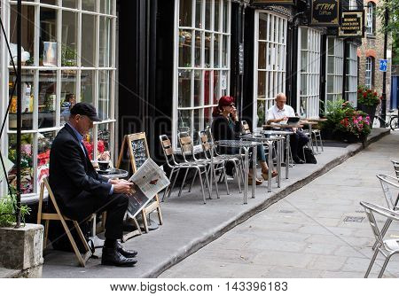 KING'S CROSS. LONDON, UK - JULY 21, 2016. Londoners relaxing at the outdoor tables of small cafes and enjoying the cafe culture in a suburb of London.