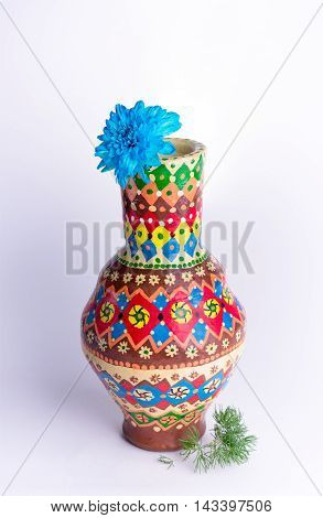 Still life composition of colorful pottery vase with one blue flower on white background