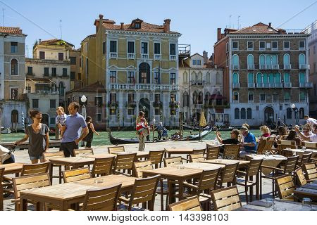 VENICE,ITALY-AUGUST 17,2014:people stroll or take a rest near the bar and restaurant on Grand canal near the Rialto bridge during a sunny day.
