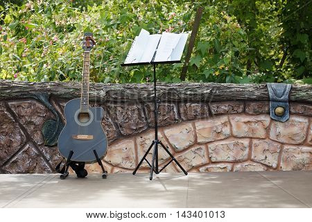 Musical concert. Acoustic guitar standing on the open stage near the fence. Behind the fence a garden.