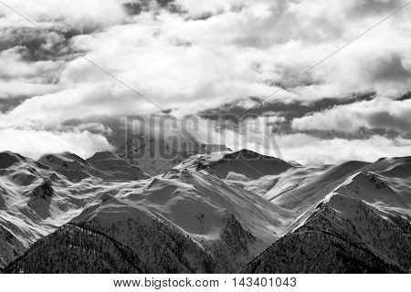 Black and white view on snowy mountains and cloudy sky at evening. Caucasus Mountains. Svaneti region of Georgia.