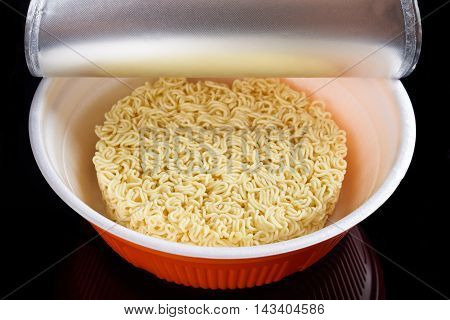 Instant noodles in plastic plate opened for preparation