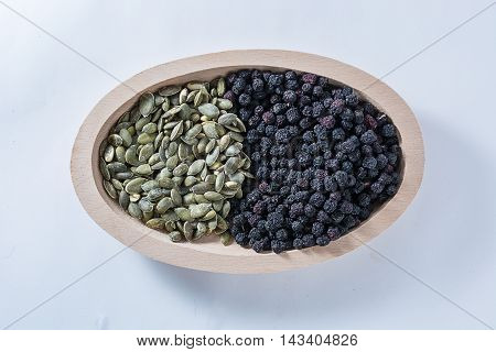 Aronia And Pumkin Seeds In Wooden Bowl