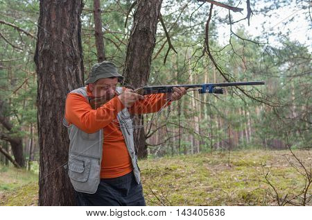 Senior hunter aim rifle in pine forest