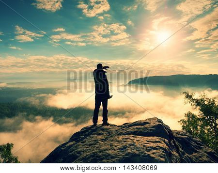 Photographer With Tripod On Cliff Shadowing Eyes And Thinking. Heavy Fogy Landscape,